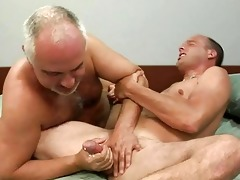 mature gay gives younger hunk a handjob on daybed